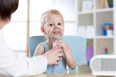 Bambino con i problemi di asma che fanno inalazione con la maschera sul suo fronte fotografie stock