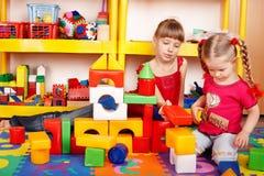 Bambino con il blocco nella stanza del gioco. Immagine Stock