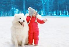 Bambino con il cane samoiedo bianco nell'inverno Fotografie Stock