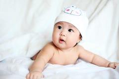 Bambino con il cappello della mucca che si riposa su una coperta bianca Immagini Stock Libere da Diritti