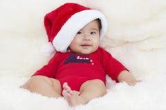 Bambino con il cappello della Santa Buon Natale e un buon anno con A Immagini Stock