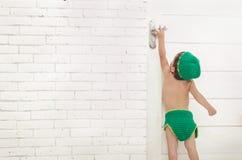 Bambino con il cappello verde ed i pantaloni che provano a raggiungere la maniglia di porta fotografia stock