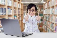Bambino con il computer portatile che dà i pollici su in biblioteca Immagine Stock