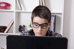 Bambino con il computer portatile del computer fotografia stock libera da diritti