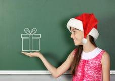 Bambino con il contenitore di regalo estratto tenuta del cappello di Santa vicino alla lavagna della scuola Fotografia Stock Libera da Diritti
