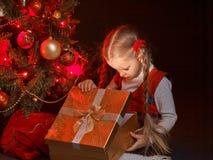 Bambino con il contenitore di regalo vicino all'albero di Natale Fotografie Stock Libere da Diritti