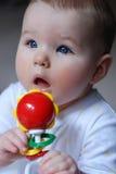 Bambino con il crepitio Fotografia Stock