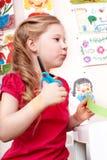 Bambino con il documento del taglio delle forbici nella stanza del gioco. fotografia stock libera da diritti