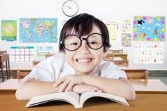 Bambino con il fronte sveglio che sorride nell'aula Fotografie Stock
