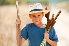 Bambino con il gioco del cappello di paglia Fotografie Stock