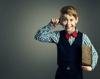 Bambino con il libro e la lente d'ingrandimento, istruzione del bambino della scuola Fotografia Stock