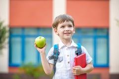Bambino con il libro e la mela verde all'aperto Fotografie Stock Libere da Diritti
