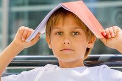 Bambino con il libro sulla sua testa Fotografia Stock