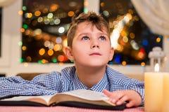 Bambino con il libro vicino alla candela fotografia stock libera da diritti