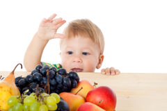 Bambino con il mucchio di frutta Immagini Stock