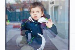 Bambino con il naso contro la finestra immagini stock