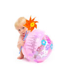Bambino con il pinwheel che si nasconde dietro la sfera di spiaggia Fotografie Stock Libere da Diritti