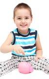 Bambino con il porcellino salvadanaio Immagine Stock