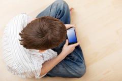 Bambino con il telefono astuto Immagini Stock Libere da Diritti