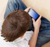Bambino con il telefono astuto Immagine Stock