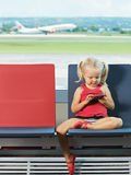 Bambino con il telefono nelle mani l'aeroporto immagine stock libera da diritti