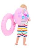 Bambino con l'anello gonfiabile che si nasconde dietro la sfera Fotografia Stock