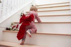 Bambino con l'arco di Natale sulle scale in pigiami Fotografia Stock Libera da Diritti