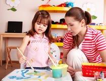 Bambino con l'insegnante in vernice di tiraggio della stanza del gioco. immagini stock