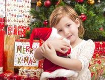 Bambino con la bambola della Santa davanti all'albero di Natale Immagine Stock
