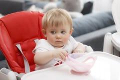 Bambino con la bionda degli occhi azzurri che si siede e che mangia porridge fotografie stock libere da diritti