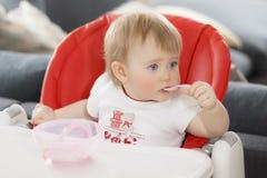 Bambino con la bionda degli occhi azzurri che si siede e che mangia porridge fotografia stock libera da diritti