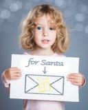 Bambino con la cartolina di Natale Fotografie Stock Libere da Diritti