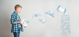 Bambino con la compressa ed i libri digitali Immagine Stock