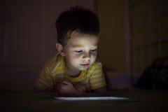 Bambino con la compressa nello scuro Fotografia Stock Libera da Diritti