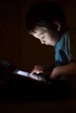 Bambino con la compressa nello scuro Fotografie Stock Libere da Diritti