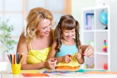 Bambino con la donna che taglia la carta di forbici dentro Fotografie Stock Libere da Diritti