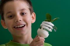 Bambino con la lampadina economizzatrice d'energia fotografie stock libere da diritti