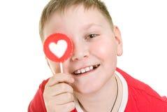 Bambino con la lecca-lecca a forma di del cuore Immagine Stock