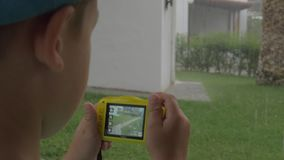 Bambino con la macchina fotografica che fa le foto durante il giorno piovoso