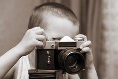 Bambino con la macchina fotografica d'annata Un bambino prende le immagini con una vecchia macchina fotografica fotografia stock libera da diritti