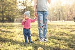 Bambino con la madre che sta insieme a tenersi per mano nel parco di estate su erba L'oggetto principale è bambino Madre irricono immagini stock libere da diritti