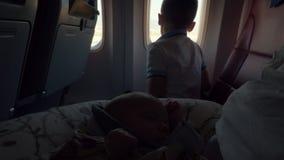 Bambino con la mamma ed il fratello in aereo di atterraggio video d archivio