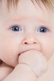 Bambino con la mano in suo primo piano della bocca immagine stock