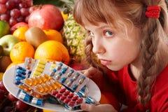 Bambino con la pillola della vitamina e della frutta. Fotografia Stock