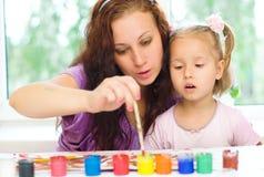Bambino con la pittura della madre Fotografie Stock