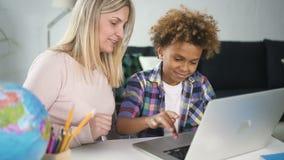 Bambino con la sua mamma della donna che si siede dietro lo scrittorio e che per mezzo del computer portatile stock footage