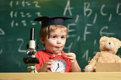 Bambino con la sveglia sulla tavola Ritratto del ragazzo sveglio che impara nell'aula Ragazzo del bambino in cappuccio accademico Immagini Stock Libere da Diritti