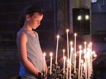 Bambino con le candele votive in una chiesa Fotografia Stock