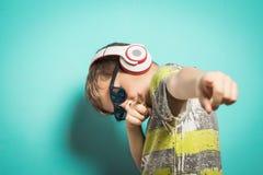 Bambino con le cuffie di musica e dell'espressione divertente fotografie stock libere da diritti