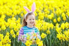 Bambino con le orecchie del coniglietto sulla caccia dell'uovo di Pasqua immagine stock libera da diritti